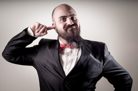bald ugly:  funny elegant bearded man with finger in the ear on vignetting background