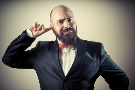 funny elegant bearded man with finger in the ear on vignetting background photo