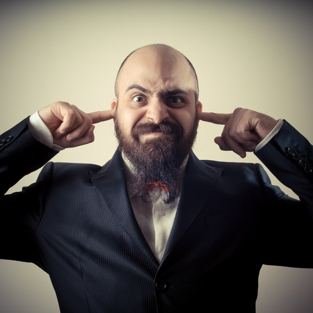 bald ugly:  funny elegant bearded man fingers in the ears on vignetting background