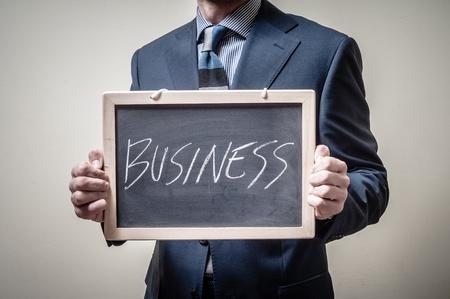 businessman holding blackboard written business on gray background photo
