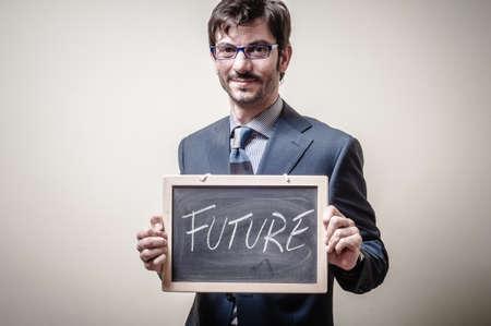businessman holding blackboard written future on gray background photo