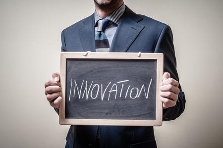 businessman holding blackboard written innovation on gray background photo
