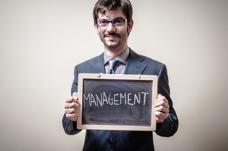 businessman holding blackboard written management on gray background photo
