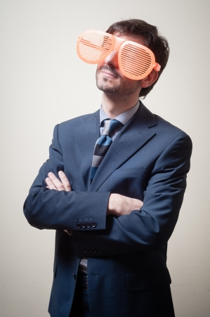 funny businessman with big orange glasses on gray background photo