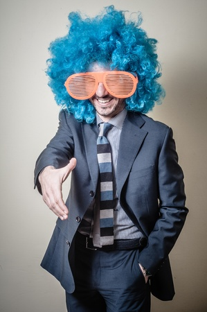 funny businessman with big orange glasses and blue wig on gray background Stockfoto