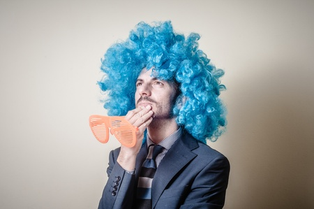 business costume: funny businessman with big orange glasses and blue wig on gray background Stock Photo