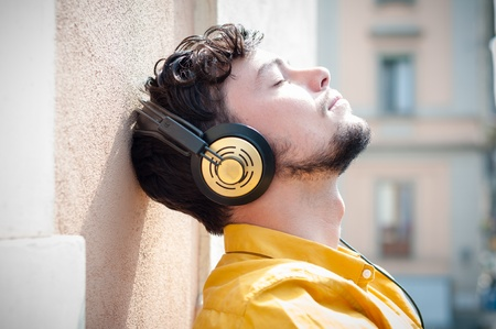 hipster young man listening to music on the balcony  photo