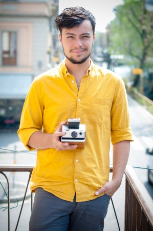 hipster young man with polaroid on the balcony photo