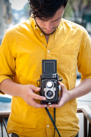 hipster young man with old camera on the balcony photo