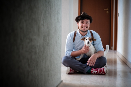 hipster young man posing with jack russell dog in a hallway photo