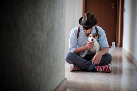 amigos abrazandose: inconformista joven posando con perro jack russell en un pasillo Foto de archivo