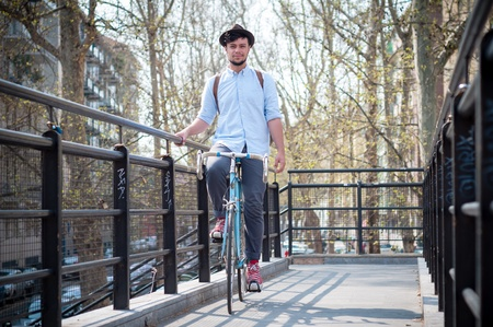 hipster young man on bike in the city photo