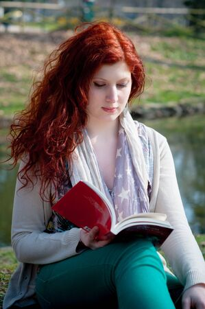 log hair: beautiful red head young woman reading book in the park Stock Photo