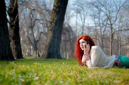 beautiful young woman on the phone in the park photo
