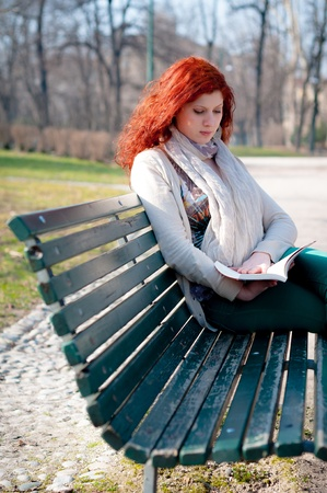 beautiful red head young woman reading book in the park photo