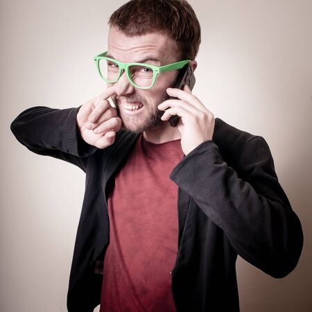 funny stylish hipster man on the phone on gray background photo