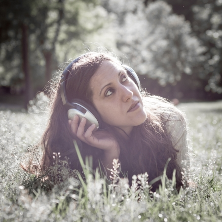 vintage hipster eastern woman with headphones in the park photo