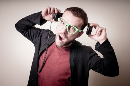 stylish hipster listening to music on gray background photo