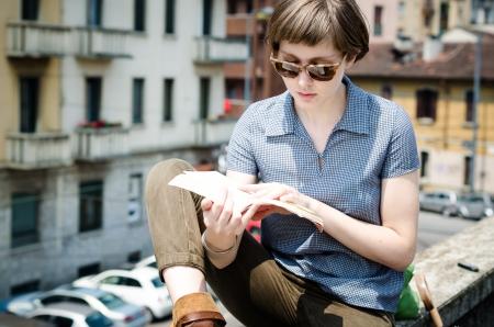mujer leyendo libro: joven y bella mujer inconformista libro de lectura en la ciudad Foto de archivo