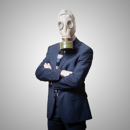 businessman with gas mask on gray background photo