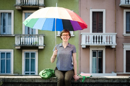 young beautiful hipster woman with colorful umbrella in the city photo