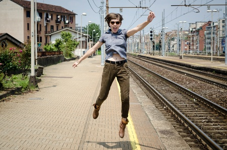 young beautiful hipster woman jumping in the station photo