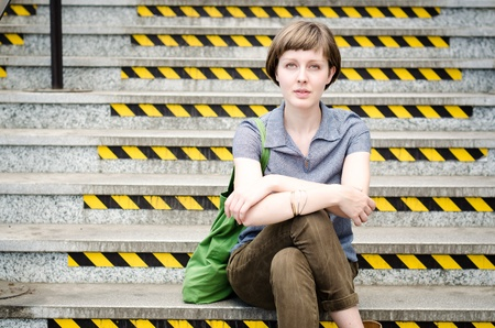 young beautiful hipster woman sitting on the stairs in the city photo