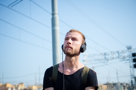 hipster modern stylish blonde man listening music in daily life photo