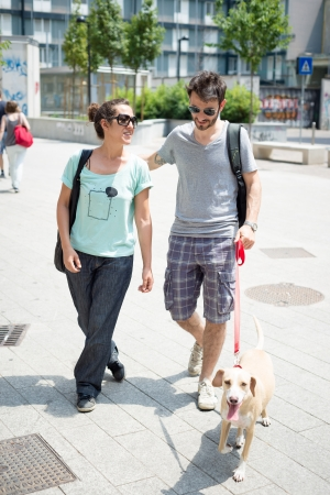 couple with dog walking in the street in the morning photo