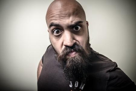 uomo barbuto guardando fotocamera con divertenti strana espressione su sfondo grigio Archivio Fotografico