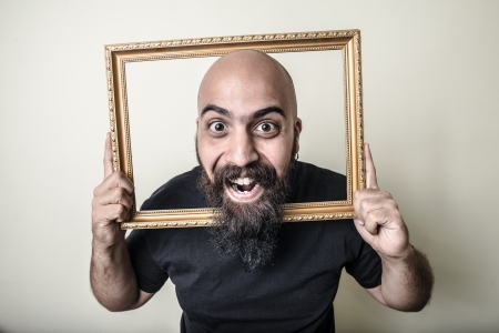 funny bearded man: funny bearded man with golden frame on gray background