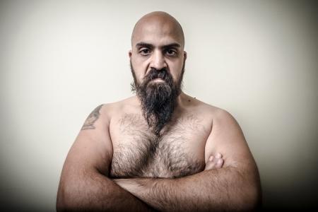 genio de la lampara: energ�a estupenda enojado muscular hombre con barba sobre fondo gris Foto de archivo