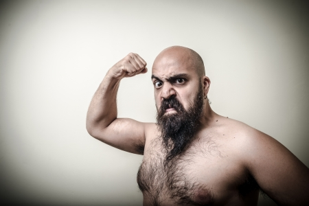 super power angry muscle bearded man  on gray background photo