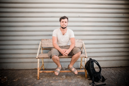 damper: stylish man sitting on a bench in the street