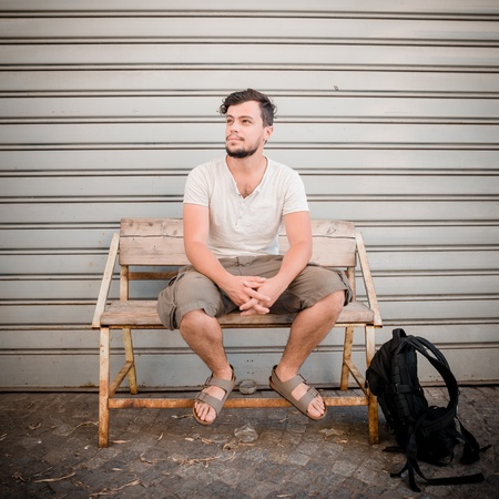 stylish man sitting on a bench in the street photo