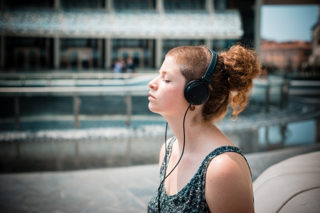 beautiful stylish modern young woman listening to music in the city photo