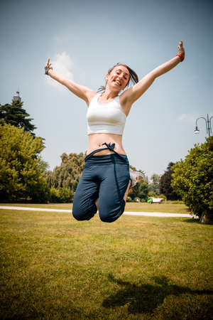 woman flying: beautiful woman fitness jumping at the park Stock Photo