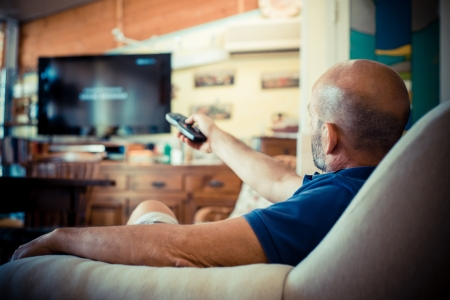 middle age man watching tv at home photo