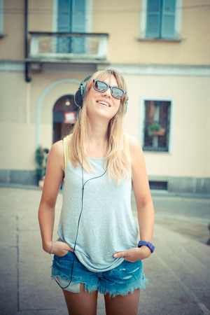 beautiful blonde woman listening to music in the city photo