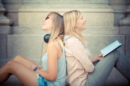 two beautiful blonde woman relaxing in the city photo
