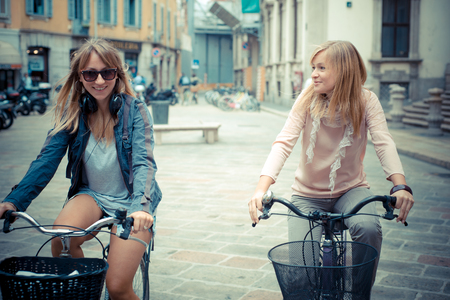 spontaneous: two beautiful blonde women shopping on bike in the city