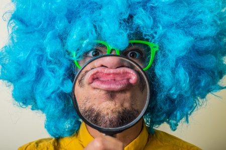 crazy funny young man with blue wig on white background Stock Photo