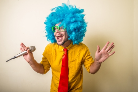 crazy funny young man with blue wig on white background photo