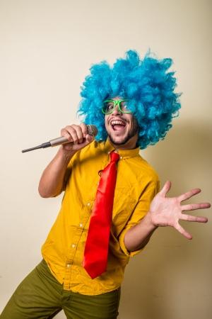 gekke grappige jonge man met blauwe pruik op witte achtergrond Stockfoto