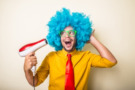 phon: crazy funny young man with blue wig on white background Stock Photo