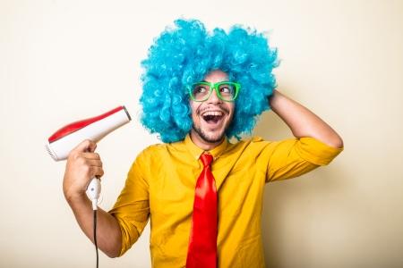 gekke grappige jonge man met blauwe pruik op een witte achtergrond
