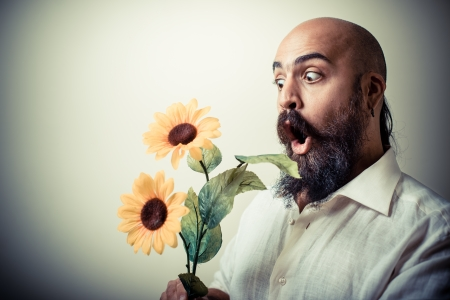 long beard and mustache man giving flowers isolated on gray  photo