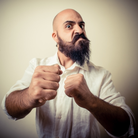 angry fighter long beard and mustache man  isolated on gray photo