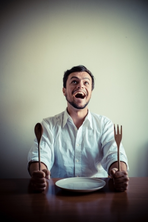 crazy man: young stylish man with white shirt eating in mealtimes behind a table