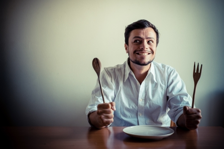 abstinence: young stylish man with white shirt eating in mealtimes behind a table